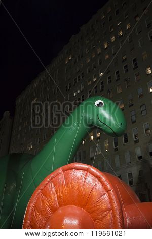 NEW YORK - NOV 25 2015: Dino, the green brontosaurus balloon from Sinclair Oil tied down during Macy's Giant Balloon Inflation event held the day before Thanksgiving in Manhattan.
