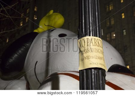 NEW YORK - NOV 25 2015: The Snoopy and Woodstock balloon from Peanuts comics in front of a No Parking sign during Macy's Giant Balloon Inflation event held the day before Thanksgiving.