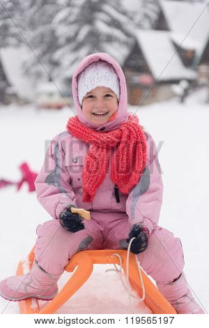 portrait of cute little girl child sitting on sledges at winter day with fresh snow,  eat cookies and have break