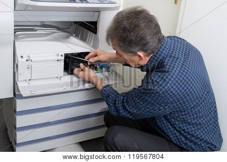 Close-up Of Man Fixing Cartridge In Photocopy Machine In Office