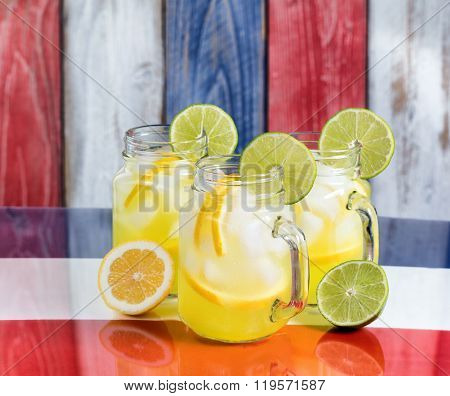 Glass Mugs Filled With Cold Lemonade On Usa National Colors For The Holiday Season