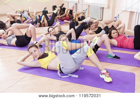 Sport, Fitness And Pilates Concepts. Group Of Seven Caucasian Female Athletes Stratching Leg Muscles