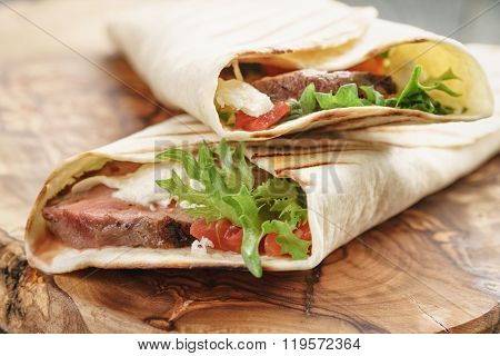 fresh homemade burritos with beef on olive cutting board