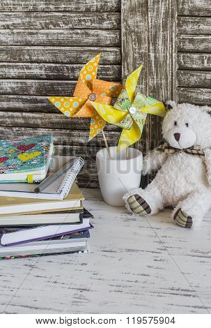 Children's Home Workspace With Books, Notebooks, Notepads, Tablet And Handmade Paper Pinwheels
