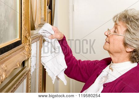 Woman dusting picture frames
