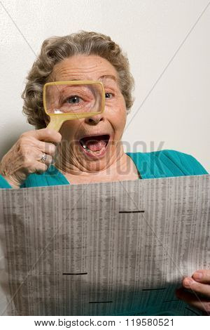 Woman reading newspaper with magnifying glass
