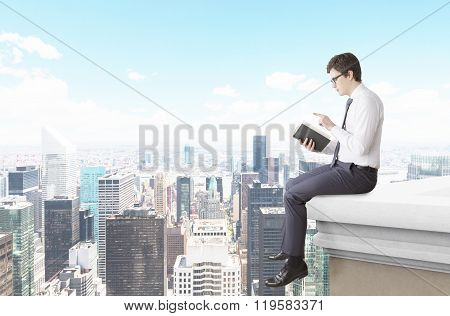 Man Reading A Book On The Roof