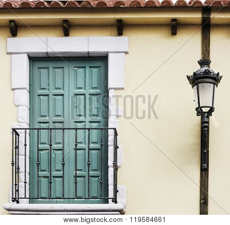 Balcony With Green Doors And Classic Lamppost On Yellow Facade