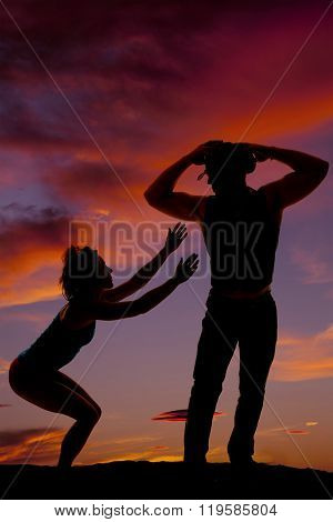 A silhouette of a woman reaching up to her cowboy.