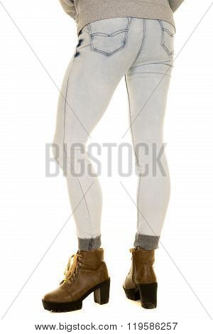 A woman standing in her jeans with her boots on.