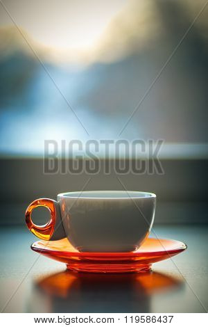 White coffee tea mug cup with orange plate in front of a window in a winter day