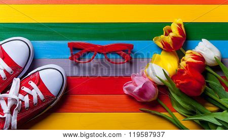 Bunch Of Tulips, Red Gumshoes And Red Glasses Lying On The Table