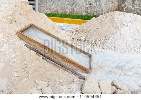 Sieve Lies On Heap Of Sand. Building Road With Paving Stone