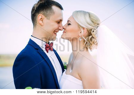 Happy And Beautiful Groom And Bride Tender Kiss At Spring Outdoors At The Beach Of The River Under B