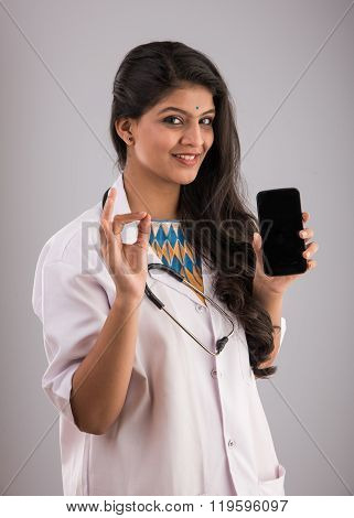 indian female doctor with smartphone, asian doctor using smartphone, isolated on gray background