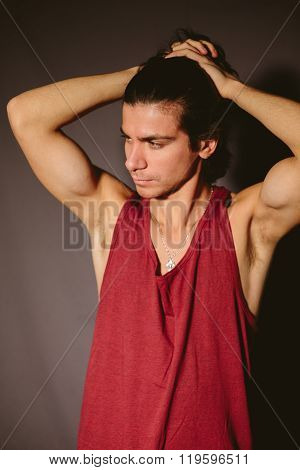 Young man the athlete in a red undershirt and hands behind the head.