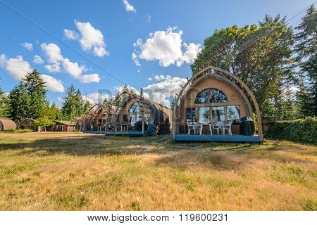 Wooden camping bungalow cottages in a forest.