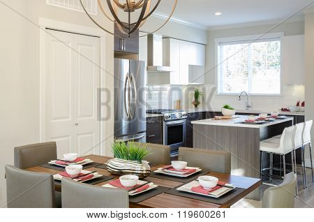 Modern dining room table with plates and bowls in a house hotel with a kitchen in the background. In