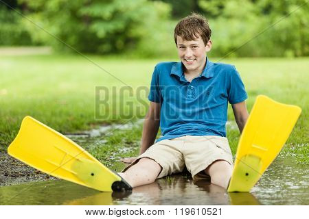 Happy Teenager Sitting In Large Puddle