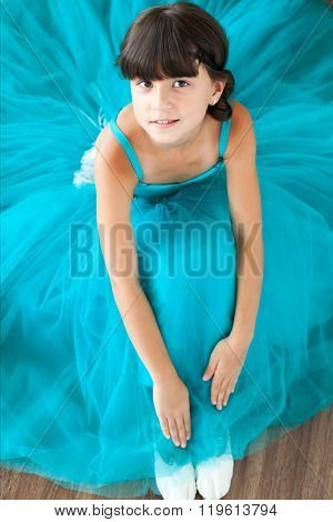 The girl in a beautiful dress sits on a floor