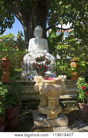Sculpture of a seated Buddha in the shade of a Bodhi tree. Nam Quang pagoda in Hoi An