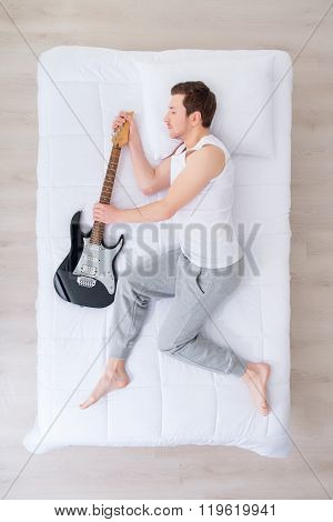 Handsome man sleeping with guitar