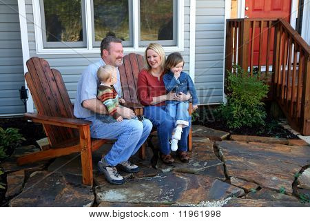A family sitting in front of their home