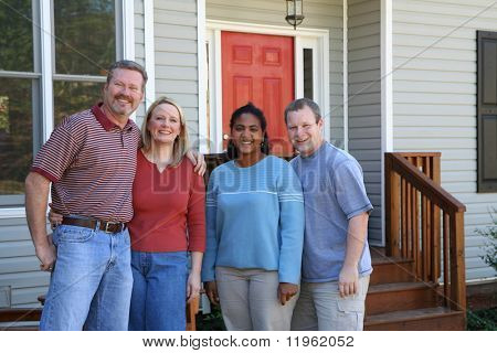 Two happy couples standing outside a new home