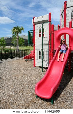 Young girl outside playing on a playground