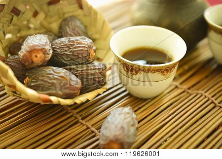 Ripened dates in a small palm basket with Arabic coffee cup. Arabian food. Stock photography.