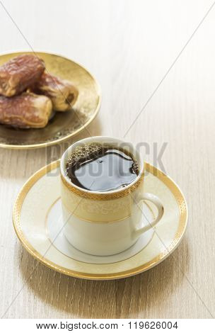 Qahva and dates. Small arabic coffee cup with ripened date fruits. Middle eastern food photography.