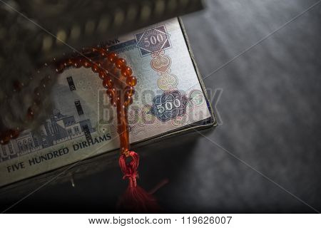 Close up of AED 500 notes in a vintage treasury box with islamic rosary. View from top.