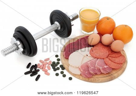 Body building dumbbell weights with supplement tablets, high protein food of chicken, steak, bacon, eggs, oranges and glass of smoothie juice over white background.