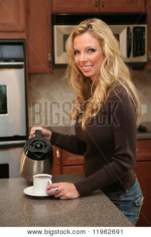 Woman drinking coffee standing in her luxury kitchen
