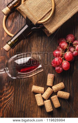 Glass With Wine, Bottle And Bunch Of Grapes, Wooden Background