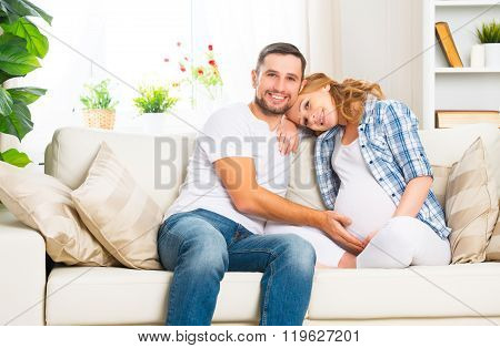 Happy Family In Anticipation Of The Birth Of Baby. Pregnant Woman And Her Husband At Home