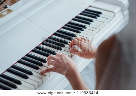 Close up of hands playing white piano. Concept of music and entertainment.