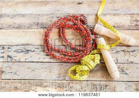 Skipping Rope And Measuring Tape On Wooden Table
