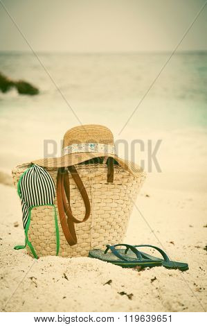 Beach holiday concept. Straw hat and bag on a tropical beach - vintage photo