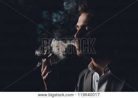 Handome Cheeky Man In Suit On The Black Background Smoking A Cigar