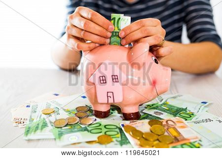 Saving concept. Women's hand puts money in piggy bank. Selective focus. Saving for a house