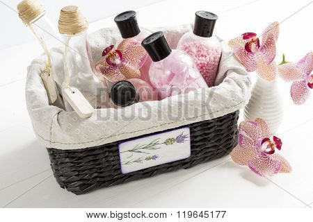 set of cosmetics for body care in a wicker basket on a white table