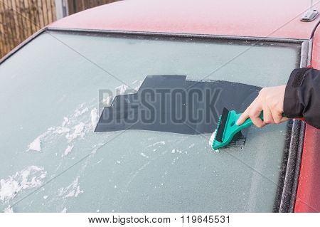 Hand Is Scraping Ice From The Windshield Of The Car