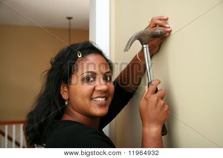 Woman hangs a picture in their new home