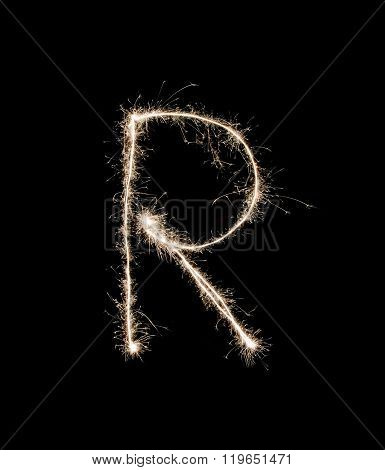 Letter R drew with spakrs on a black background.