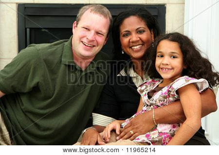 Interracial family sitting together at home