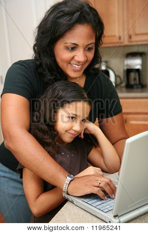 Woman in her kitchen with daughter on the computer