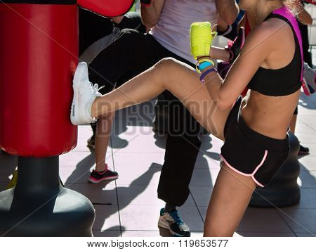 Young Girl Doing Kickboxing With Gloves In Fitness Class With Red Punching Bag