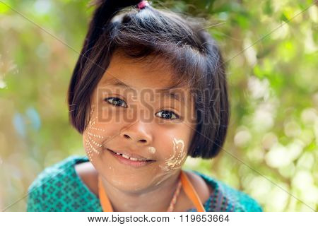 SANGKHLABURI, THAILAND, JANUARY 24, 2016 : A Thai little girl selling souvenir stuffs is posing near a temple in Sanghlaburi, Thailand