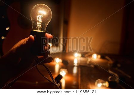 Incandescent light bulb, warm turned on. Garland of tungsten lamps. Light in darkness, copy space.